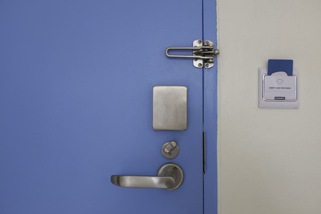 blue door with stainless steel handle lock set and access control card in socket on wall Stock Photo