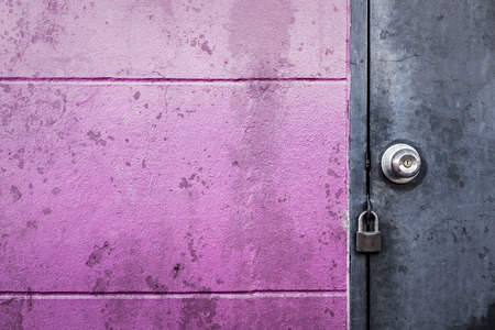 groove: rustic grey metal door with knob and lock on dirty stain texture groove wall Stock Photo