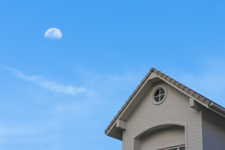new traditional gable roof house under blue moon cloud sky