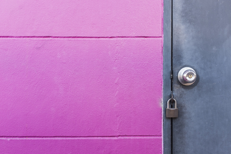 rustic grey metal door with knob and lock on texture groove pink wall
