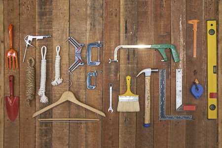 various kind of hand tools and equipments hang on vertical stripe wood board