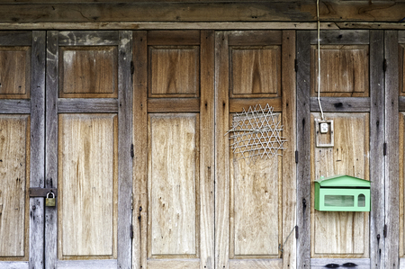 old traditional thai folding wood door panel ornament with rustic lock set vintage bell ring switch and new green metal mail box