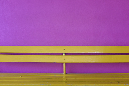 bright yellow wood bench on vivid violet color wall background