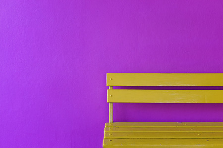 partial bright yellow wood bench on vivid violet color wall background