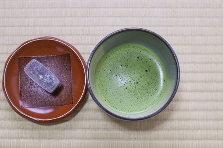 fresh japanese green tea with sugar and bean dessert in traditional cup and plate on tatami mat background Stock Photo