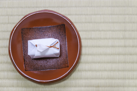 japanese traditional dessert in white paper wrap with red rope in red plate on tatami mat Stock Photo