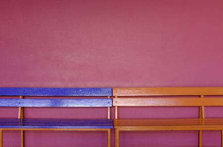 abstract colorful blue and orange long wood bench on vivid pink color wall background