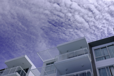 low angle view of low rise modern architecture in blue cloud sky