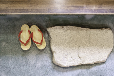 pair of japanese traditional shoe on stone floor with stone and wood step Stock Photo