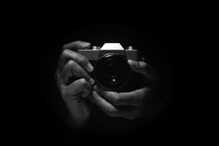 two hand holding vintage retro style camera with lens in low key light