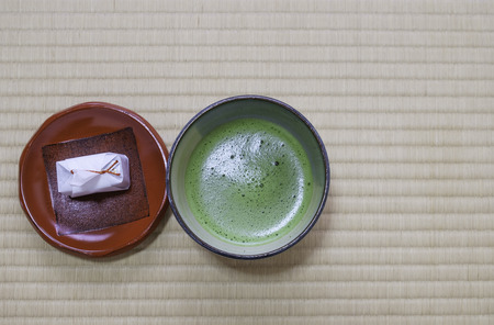 fresh japanese green tea with white paper wrap dessert in traditional cup and plate on tatami mat background Stock Photo
