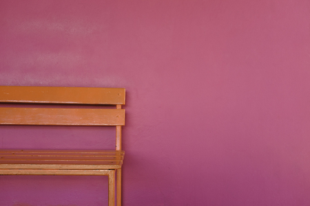 patrial bright orange wood bench on vivid pink color wall background