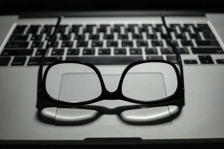 black vintage eye glasses on laptop trackpad computer with keyboard in background low key light Stock Photo