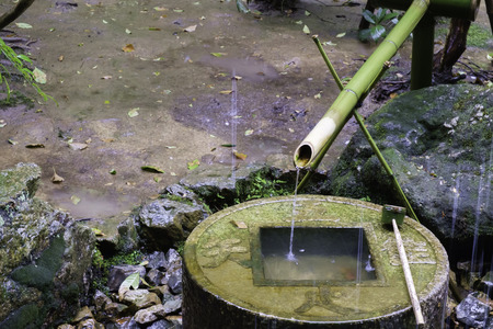 japanese bamboo water fountain feature on round engrave lettering granite stone base container with rain drop falling on Stock Photo