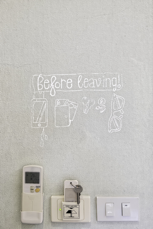 lovely handwriting warning sign to not forget belonging in white color with air-condition remote control key and light switch on texture wall