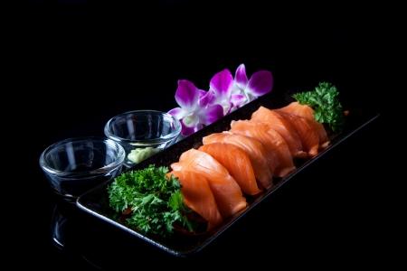 Salmon sashimi served with soy sauce and wasabi.