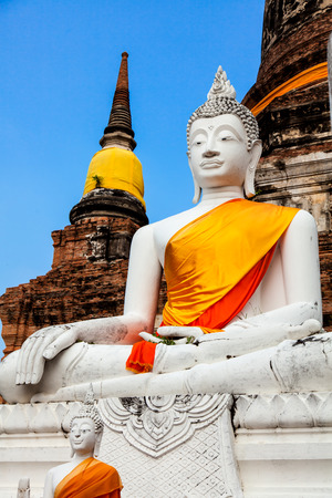 thai believe: White Buddha image in front of pagoda.