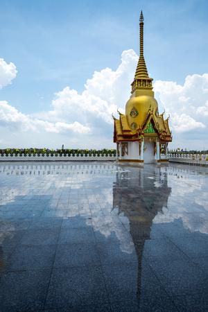 reflexion: Pequeña pagoda en el templo de Tailandia con el cielo azul y la reflexión en el suelo.
