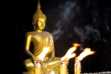 luz de las velas delante de la imagen de Buda.