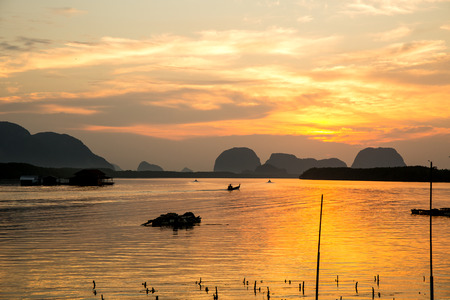 Golden light of sunrise over fisherman village by the sea. Stock Photo