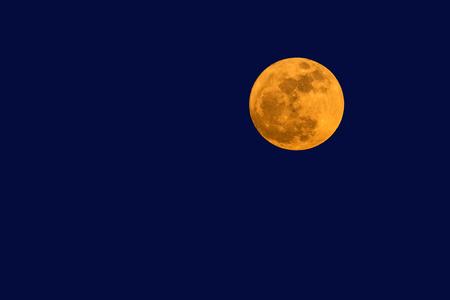 Big full moon in twilight sky.
