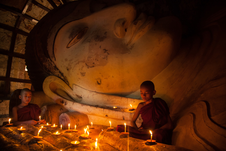 BAGAN, MYANMAR - November 4, 2013: Neophyte (young Buddhist monk) praying with candle light in front of Buddha image. Editöryel