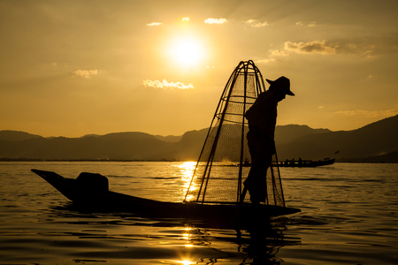 Inle Lake, Myanmar - Nov 2013: Burmese man rowing a small boat in Inle Lake. The Inle natives are famous for their unique leg rowing technique. Editorial