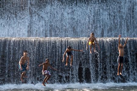 Bali, Indonesia - June 10,2017: Children enjoy playing jump into the water at  Klungkung Dam or Dam Tukad Yeh Unda. Redakční