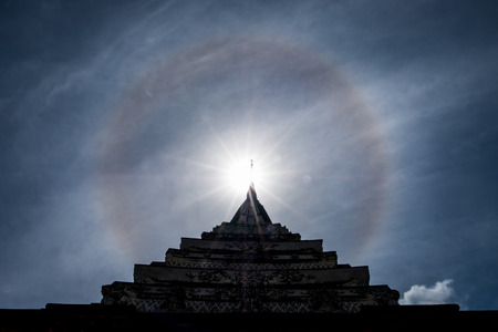 Sun halo over Thai temple roof, Thailand.