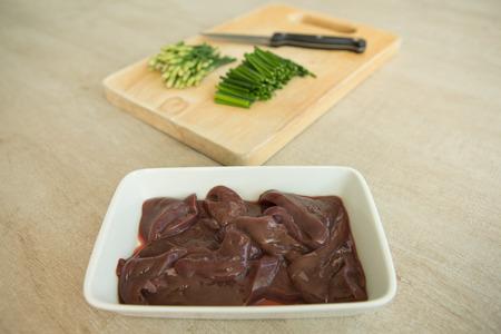 plato del buen comer: hígado de cerdo con las cebolletas chinas en picado de madera, preparación de alimentos