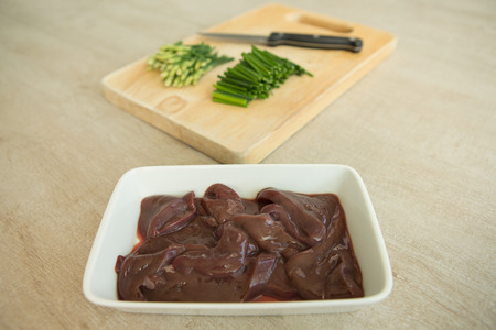plato del buen comer: pork liver with Chinese chives on Chopping Wood, food preparation