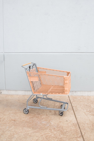 Shopping cart with orange basket outside the store