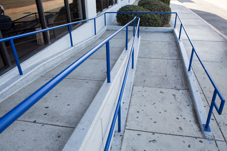 ramp way with blue handrail for support wheelchair disabled people. Imagens