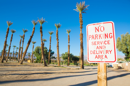 No Parking sign with palm trees and blue sky Stock Photo
