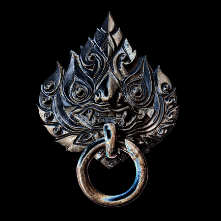 The ancient thai styles door handle or door knocker made from brass isolated on black background Stock Photo