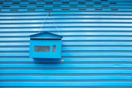 postage: blue mailbox hanging on the roller shutter door