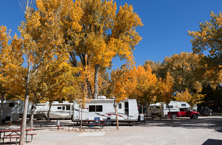 Vintage American mobile home on a camping site in Zion National Park with autumn tree