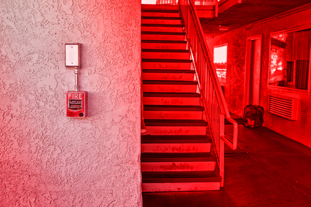 Red fire alarm switch at cement wall inside the motel building