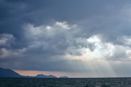 View of thunderstorm clouds with ray light above the sea Stock Photo