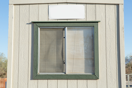 jalousie: old window with plastic window blinds on wood walls.