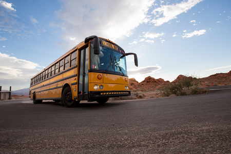 Yellow school bus on the road in Grand Canyon, USA