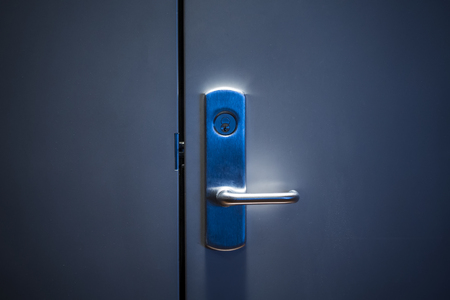 Modern metal door handle with security system lock  Foto de archivo