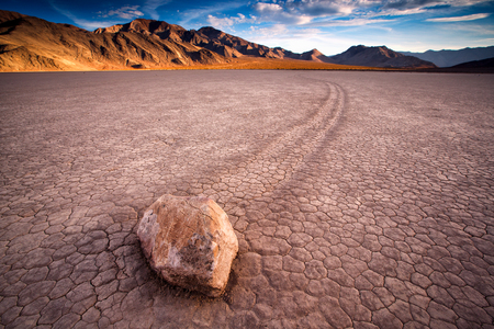 "sunset view of The Racetrack Playa, or The Racetrack, is a scenic dry lake feature with ""sailing stones"" that inscribe linear ""racetrack"" imprints."