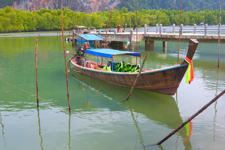 fishing boat or thai long tail boat on the beautiful color of water parking at the pier