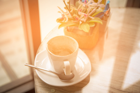 Empty coffee cup and flower on the table in cafe