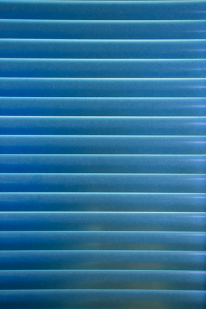 Horizontal pattern of blue venetian blinds in a gradation of color