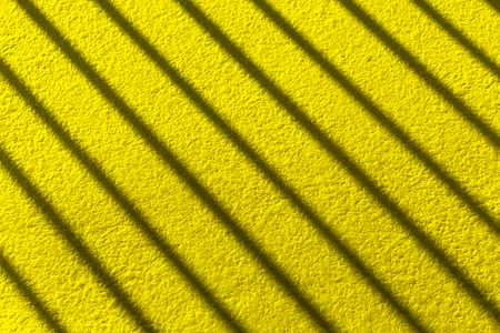 Stripe shadow on yellow cement floor or cement wall