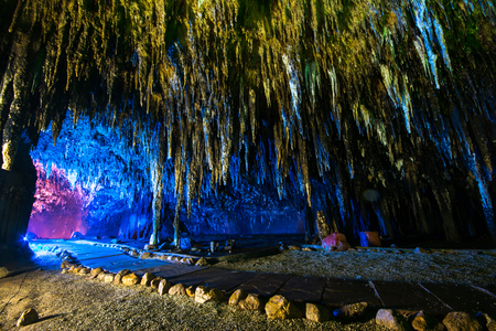 Stalactite in cave interior with color light at Khao Bin cave, Ratchaburi Thailand.