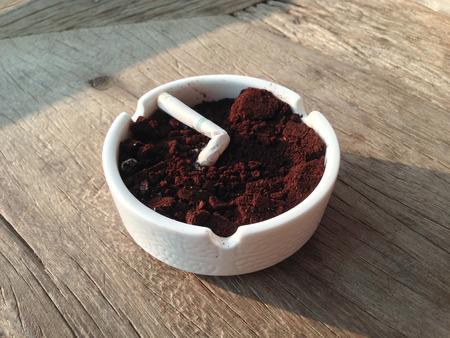 Smoked Cigarette in White Ashtray on Table Stock Photo
