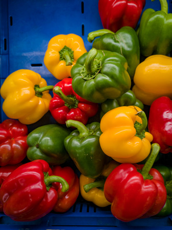 It's a photo of red, yellow and green bell peppers in close up in a blue basket or crate in a supermarket.